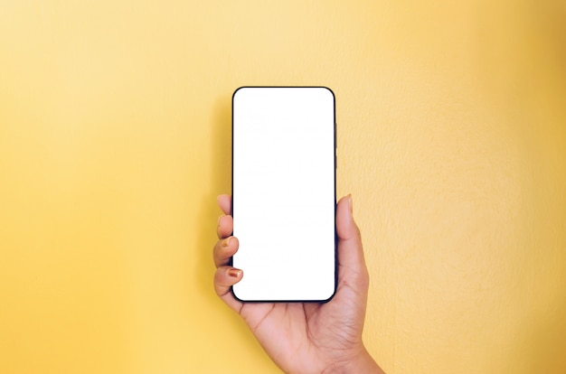 Human hand holding smartphone with white screen background. Premium Photo