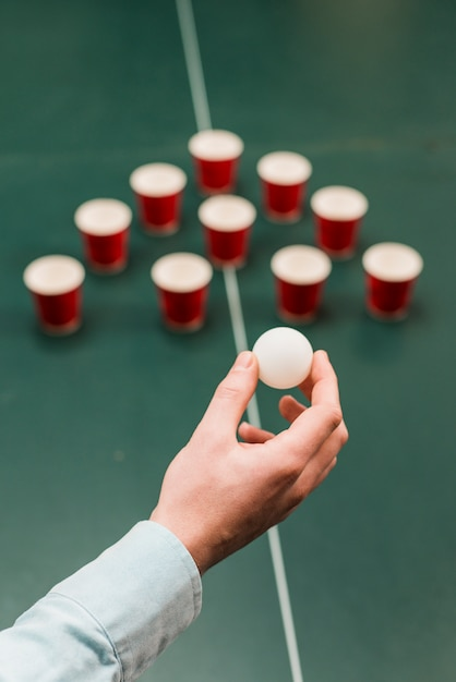 Human hand holding white ball for playing beer pong game Free Photo