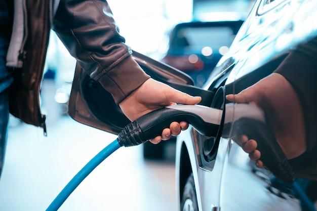 La mano umana sta tenendo la ricarica dell'auto elettrica connessa all'auto elettrica Foto Gratuite