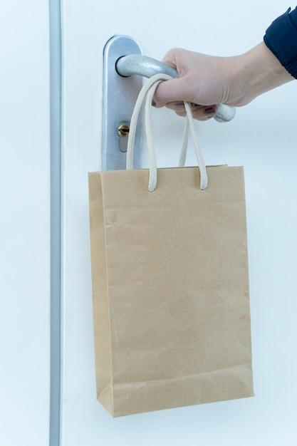 人間の手が鍵のかかったドアを開こうとし、食べ物の紙袋が手首にかかっています。 Premium写真