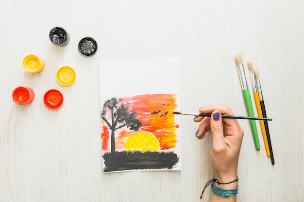 Human hand painting a beautiful nature sunset seen on paper with water colors Free Photo