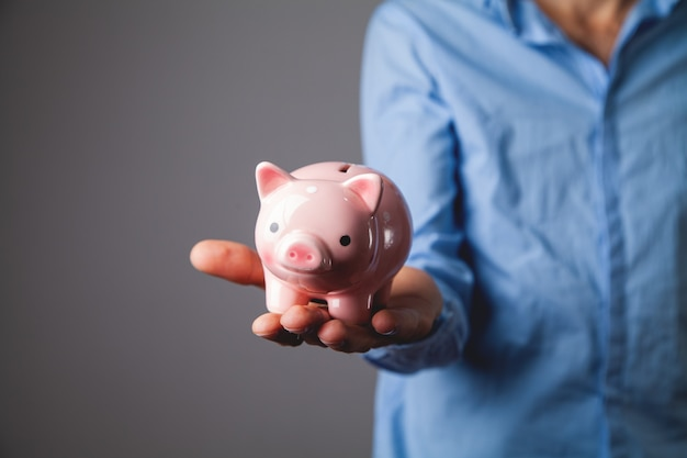 돼지 저금통을 보호하는 인간의 손 프리미엄 사진