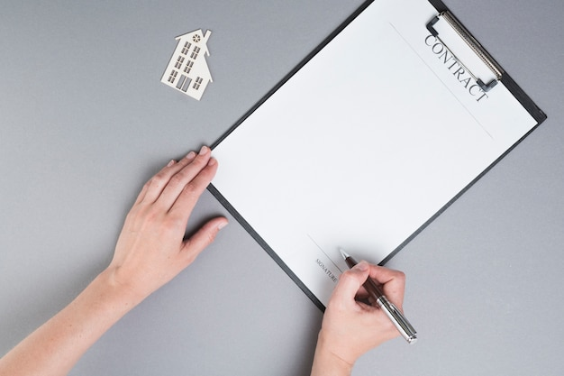 Human hand signing on contract paper near paper house cutout over grey background Free Photo