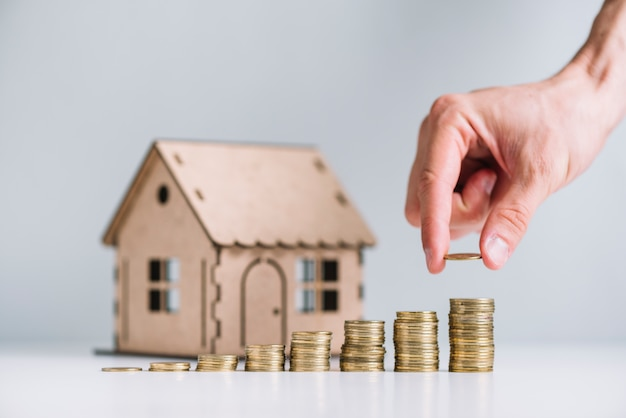 Human hand stacking coins in front of house model Free Photo