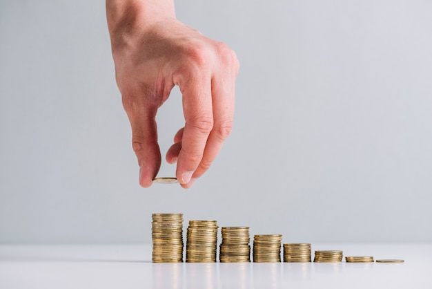Human hand stacking golden coins on reflective desk Free Photo