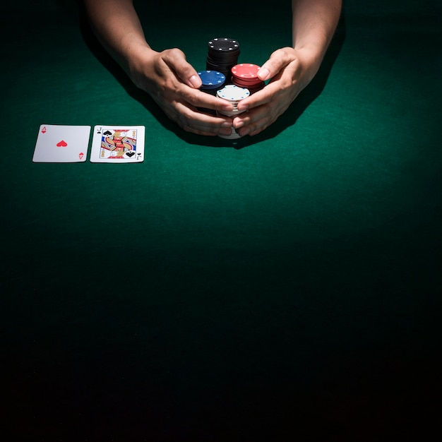 Human hand taking stack of poker chips on casino table Free Photo