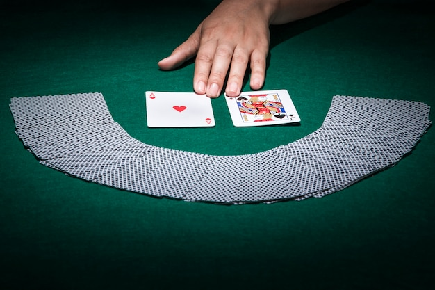 jouer carte sur table Human hand touching playing card on poker table | Free Photo