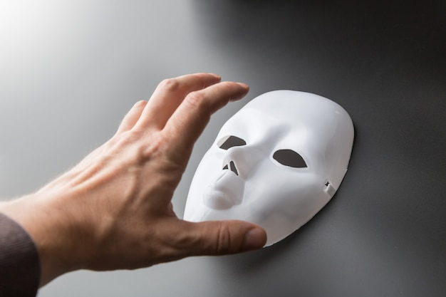 Human hand tries to take theater mask on grey Premium Photo