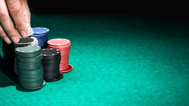 Human hand with casino chips on green table Free Photo