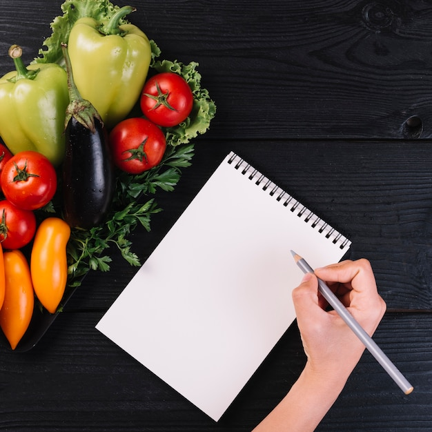 Human hand writing on spiral notepad with fresh vegetables on black wooden backdrop Free Photo