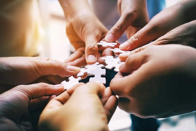 Human hands assembling jigsaw puzzle,searching for right match Premium Photo
