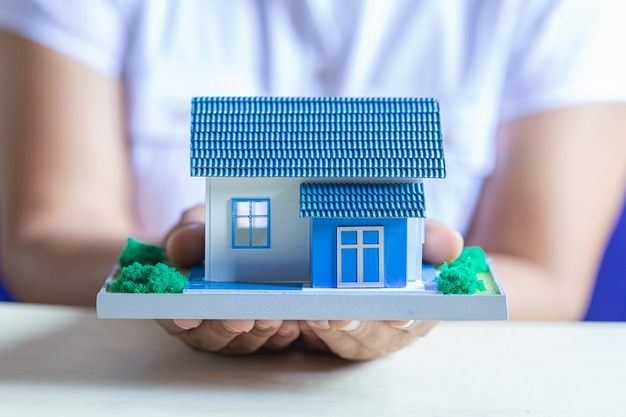 Human hands holding model of dream house Free Photo