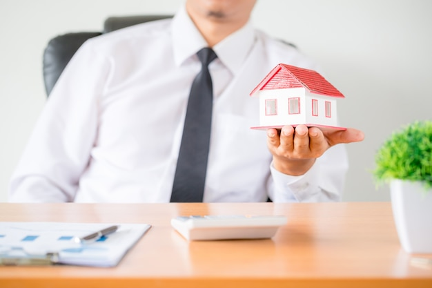 Human hands holding model of dream house. Free Photo