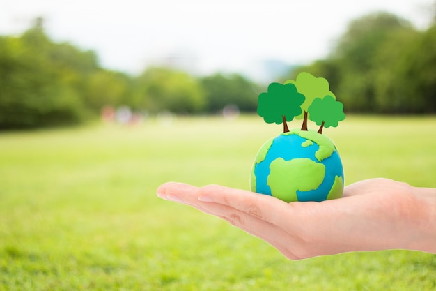 Human hands holding plant trees on the globe, planet or earth over blurred green garden nature background. ecology concept. Premium Photo