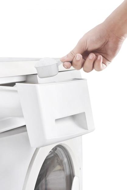 Human hands put the detergent into the washing machine Premium Photo