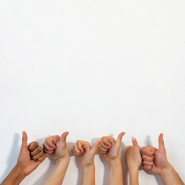 Human hands showing thumbup gesture over white textured wall Free Photo