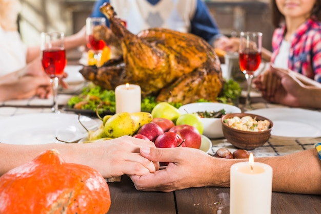 Human holding hands at table with food Free Photo