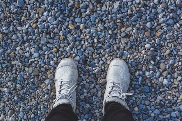 Gambe umane in scarpe da ginnastica bianche in piedi sulla spiaggia sassosa Foto Gratuite