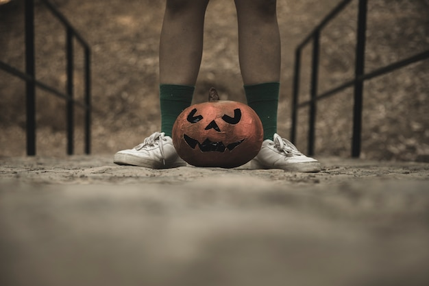 Human legs with halloween pumpkin placed on walkways in park Free Photo