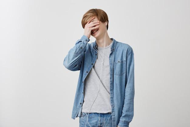 Человек, досуг и современные технологии концепции. в помещении выстрел светловолосого юноши в джинсовой рубашке, слушает песни в наушниках, ничего не слышит, прячет лицо за ладонью. Бесплатные Фотографии