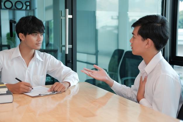 Менеджер отдела кадров проводит собеседование с кандидатом на вакансию. заявитель объяснить профиль для карьерного набора Premium Фотографии