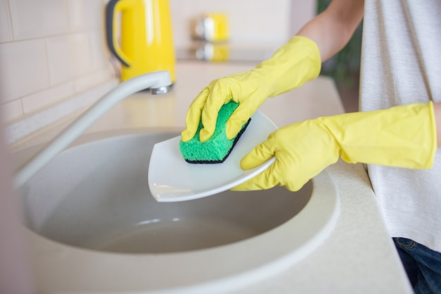 Human's hands washing the dishes. people uses green sponge and wears yellow gloves. Premium Photo