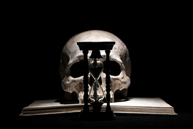 Human skull on old open book with vintage hourglass on black . Premium Photo