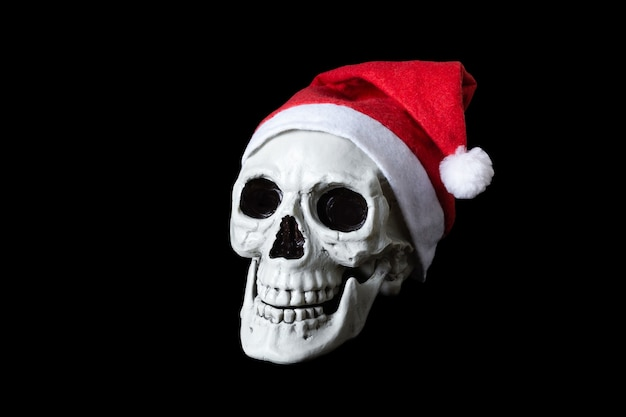 Human skull in red cap of santa claus. isolated on black surface. Premium Photo