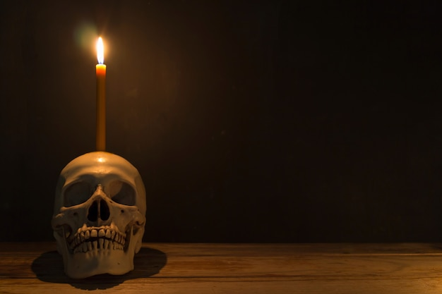 Human skull with candle light on wooden table in the dark background Premium Photo