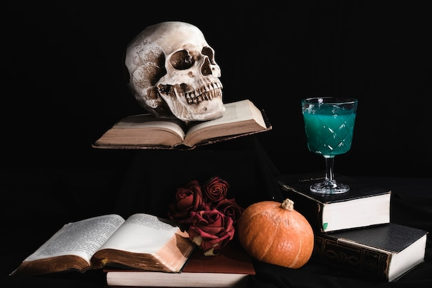 Human skull with green drink and books Free Photo