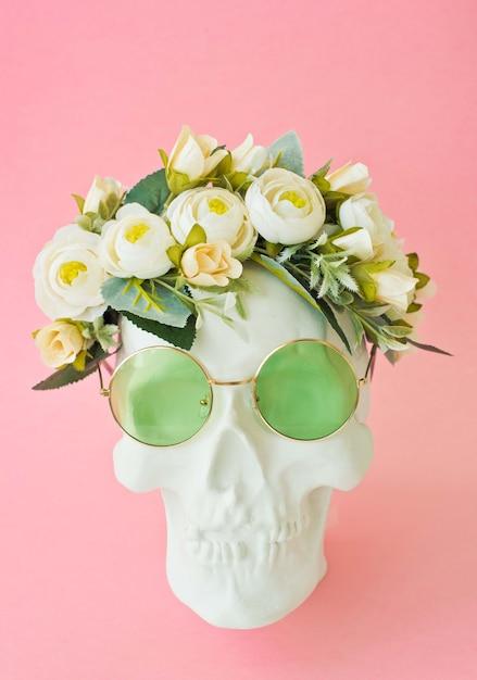 Человеческий череп с зелеными очками и цветами на белом фоне Premium Фотографии