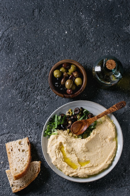 Hummus with olives and herbs Premium Photo