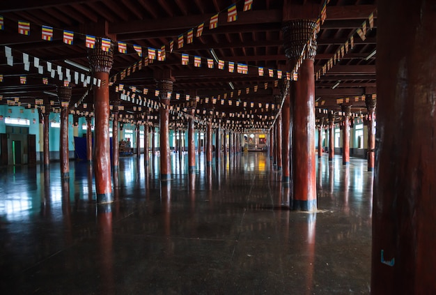 Hundred of wooden structural columns and buddhist prayer flags Premium Photo