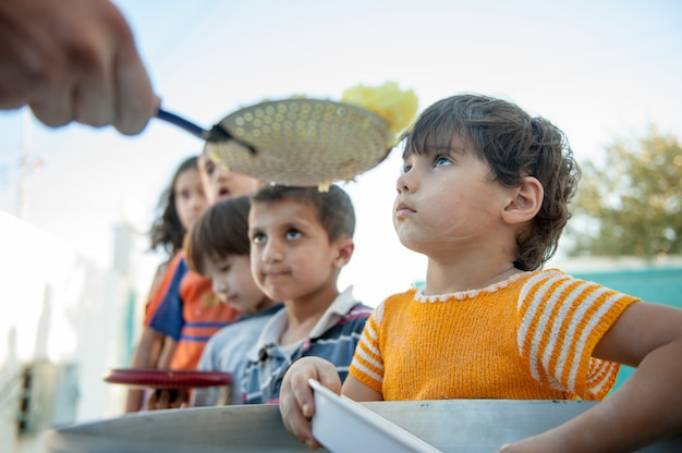 Hungry children being fed by charity Premium Photo