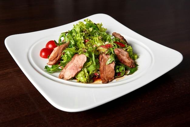 Голодные крупным планом нарезанный стейк на гриле, подается с салатом из зеленых листьев и помидорами черри на белой квадратной пластине на столе в ресторане. Бесплатные Фотографии