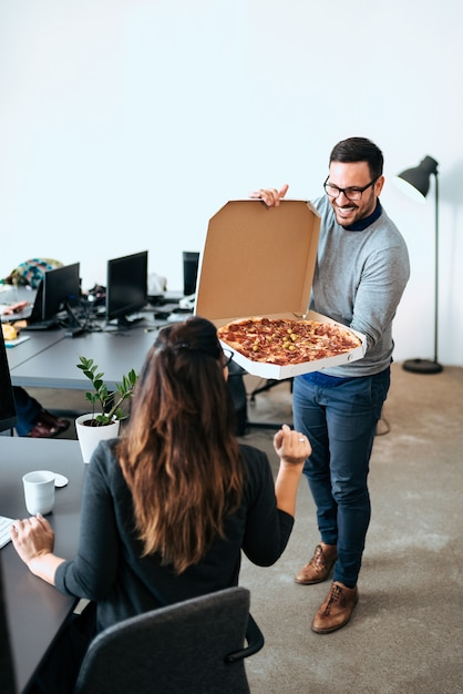 Hungry coworkers having lunch break at workplace. eating pizza. Premium Photo