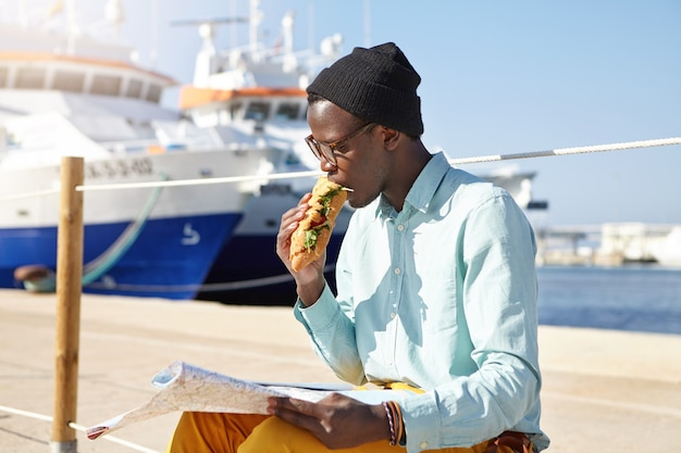 Hungry male tourist in trendy clothing and accessories eating a sandwich Free Photo
