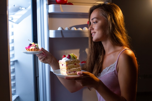 Hungry woman in pajamas eats and enjoys cakes  at night near refrigerator. stop diet and gain extra pounds due to carbs food and unhealthy night eating Premium Photo