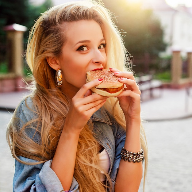 Hungry young woman eating a tasty burger Free Photo