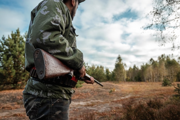Hunter with a gun in his hands in hunting clothes in the autumn forest Premium Photo