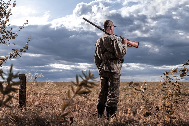 Hunter with a gun on his shoulder against the background of the field. hunting for wild animals. copy space Premium Photo