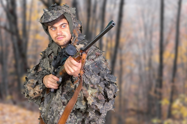Hunter with his rifle in a forest Premium Photo