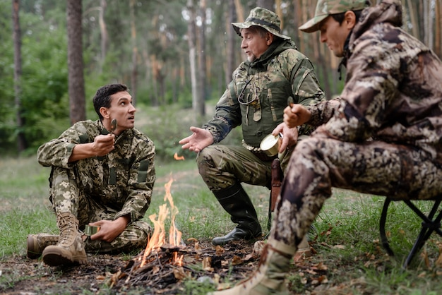 Hunters at camp fire men have food and talk. Premium Photo