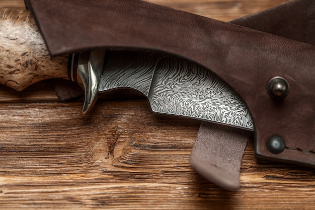 Hunting damascus steel knife handmade on a wooden surface Premium Photo