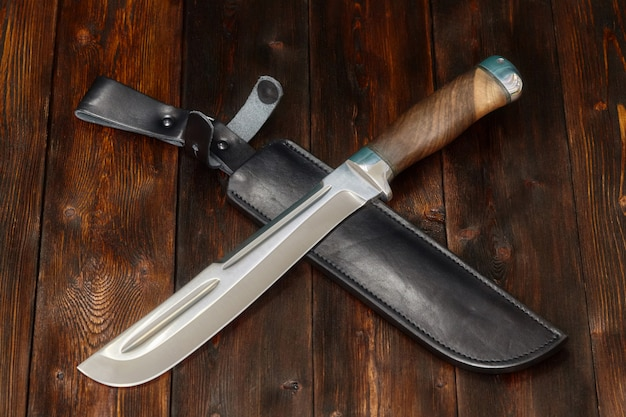 Hunting steel knife handmade on a wooden surface Premium Photo