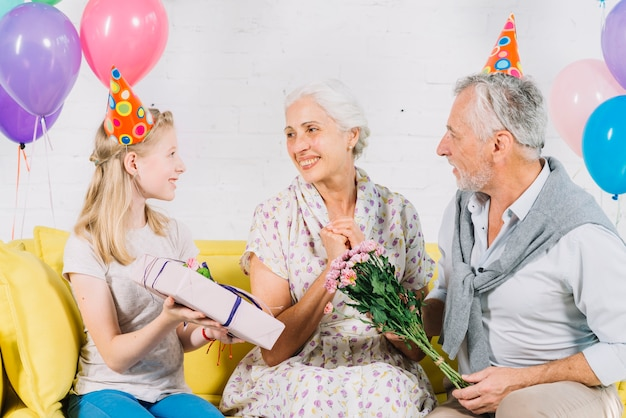 Husband And Granddaughter Giving Birthday Gift To Happy Woman Free Photo