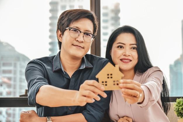 Муж и жена покупают дом, крупный план рука держит дом модель Premium Фотографии