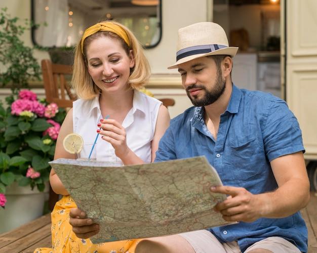 夫と妻がキャラバンの横にある地図を見る 無料写真