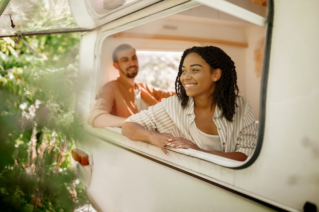 남편과 아내는 트레일러에서 캠핑을하며 Rv 창밖을 내다 봅니다. 남자와 여자는 밴, 캠핑카에서의 낭만적 인 휴가, 캠핑카의 캠핑 레저 프리미엄 사진
