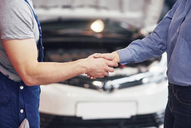 Муж автомеханик и женщина заказчик заключают договор на ремонт автомобиля Бесплатные Фотографии